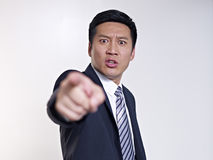 Asian businessman. Angry asian businessman pointing at camera, focus on face Stock Photo