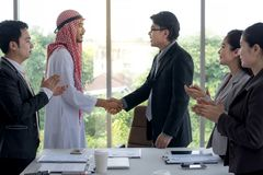 Asian businessman and Arabian businessman success in the deal shaking hands with business people clap their hands. In the meeting room Royalty Free Stock Photo