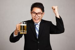 Asian businessman with beer happy pump fist up. On gray background Royalty Free Stock Images