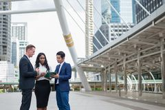 Asian businessman, black business woman and caucasian businessman holding document file on hand and talk about business plan. Asian businessman, black business royalty free stock photos