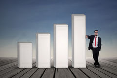 Asian businessman in black suit standing next to bar chart stock illustration