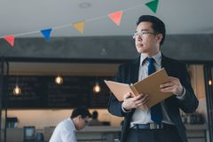 Asian businessman in black suit standing and holding document file about financial report on hand. Asian businessman in black suit, who standing and holding stock image
