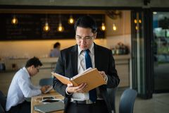 Asian businessman standing and holding document file about financial report on hand. Asian businessman in black suit, who standing and holding document file royalty free stock photo