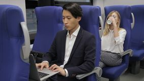 The asian businessman and blond female travel by train and sit one after another. The man in black siut and with stylish haircut works on his laptop and the stock video