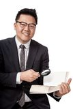 Asian businessman with book and magnifying glass Royalty Free Stock Image