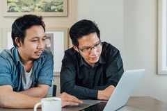 Asian businessman or business partner discussing project together using laptop computer at coffee shop. Team meeting or teamwork Stock Images