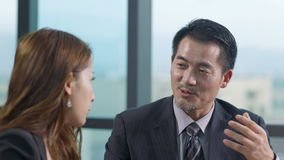 Asian businessman and businesswoman discussing business in office