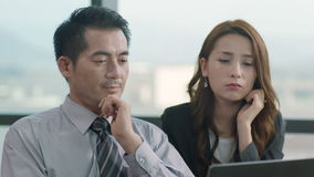 Asian businessman and businesswoman discussing business in office stock video footage