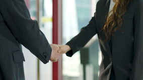 Asian businessman and businesswoman shaking hands. Asian businessman and businesswoman in formal wear shaking hand in company lobby stock video