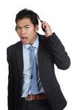 Asian businessman can't hear you. Pull  headphones asked what did you say isolated on white background Royalty Free Stock Images