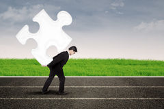 Asian businessman carry puzzle on the road royalty free stock photography
