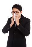 Asian businessman caught cold. Sneezing into tissue. Royalty Free Stock Images