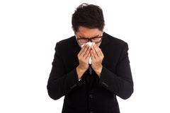Asian businessman caught cold. Sneezing into tissue. Royalty Free Stock Photography