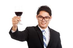 Asian businessman cheers with glass of red wine. Isolated on white background Stock Photos