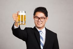 Asian businessman cheers with mug of beer. On gray background Stock Image