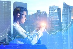 Asian businessman in city, graphs stock photo