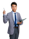 Asian businessman with clipboard and pen point up Royalty Free Stock Photography