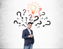 Asian businessman with coffee with question marks and bulb Royalty Free Stock Image