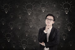 Asian businessman concentrating on lightbulbs blackboard Royalty Free Stock Images