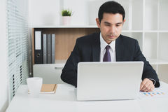 Asian businessman concentrating on using laptop computer Royalty Free Stock Image