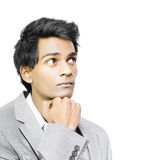 Asian businessman in deep contemplation. Young handsome Asian businessman in deep contemplation with his chin resting on his hand as he mulls over important stock photography