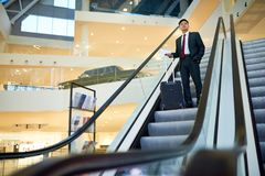Asian Businessman Descending Escalator. Full length wide angle portrait of successful Asian businessman descending on escalator holding suitcase in modern Stock Photo