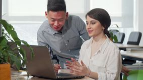 Asian businessman discussing startup ideas with his female colleague. Beautiful female entrepreneur talking to her co-worker, using laptop. Communication stock video