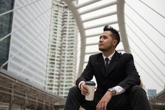 Asian businessman drink coffee in city. Young Asian businessman in Bangkok urban city drink hot coffee on paper grass and think about business project plan. He royalty free stock image