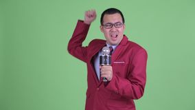 Asian businessman with eyeglasses singing with microphone. Studio shot of Asian businessman wearing red suit and eyeglasses against chroma key with green stock video