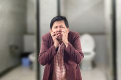 Asian Businessman feel pain with constipation and crumpled face. In front of the bathroom Stock Image
