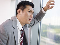 Asian businessman. Frustrated asian businessman looking out of window in office Royalty Free Stock Image