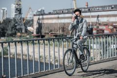 Asian businessman in gas mask riding bicycle on bridge and talking by smartphone air. Pollution concept stock photos