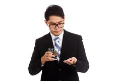 Asian businessman get sick with medicine and glass of water Royalty Free Stock Images