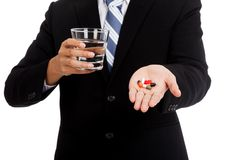 Asian businessman get sick with medicine and glass of water Stock Image