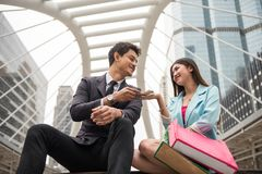 Asian businessman giving US dollar moneys to girlfriend. Asian businessman giving US dollar moneys to beautiful girlfriend or wife to shopping in Bangkok urban Royalty Free Stock Photography