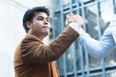 Asian businessman grasping hands with his trusted colleague Royalty Free Stock Images