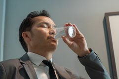 Asian Businessman in grey suit drinking water. Healthy. Copy spa Royalty Free Stock Images