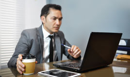 Asian Businessman in grey suit sitting and holding cup of coffee Royalty Free Stock Photos