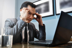 Asian Businessman in grey suit thinking and looking to his lapto Stock Photo