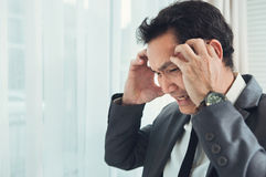 Asian businessman having headache from migraine from overworked. Il Stock Photos