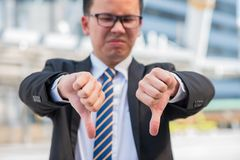 Hand symbol, unsuccessful and fail. Asian businessman with his hand showing unsuccessful and fail symbol royalty free stock photo