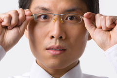 Asian businessman holding glasses to camera Stock Photography