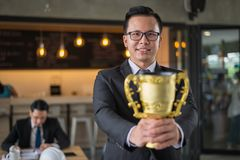Asian businessman holding a golden trophy cup to cheerful and celebrated his successful in career and mission. concept of winner. Asian businessman raising up royalty free stock photos
