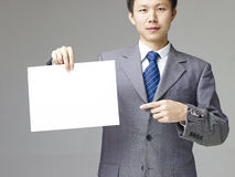 Asian businessman holding a piece of blank paper Royalty Free Stock Photo