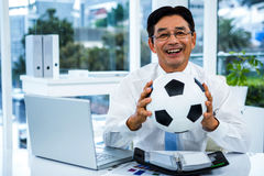Asian businessman holding soccer ball Stock Photos