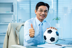 Asian businessman holding soccer ball with thumps up Stock Image