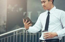Asian businessman holding tablet and looking email in morning. royalty free stock photography