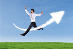 Asian businessman jumping over up arrow sign cloud Stock Images