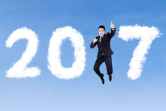 Asian businessman jumping with 2017. Young Asian businessman wearing formal suit and jumping on the blue sky with clouds shaped number 2017 Stock Photo