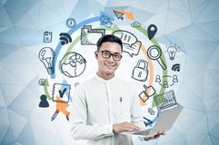 Asian businessman with laptop, computer icons stock images